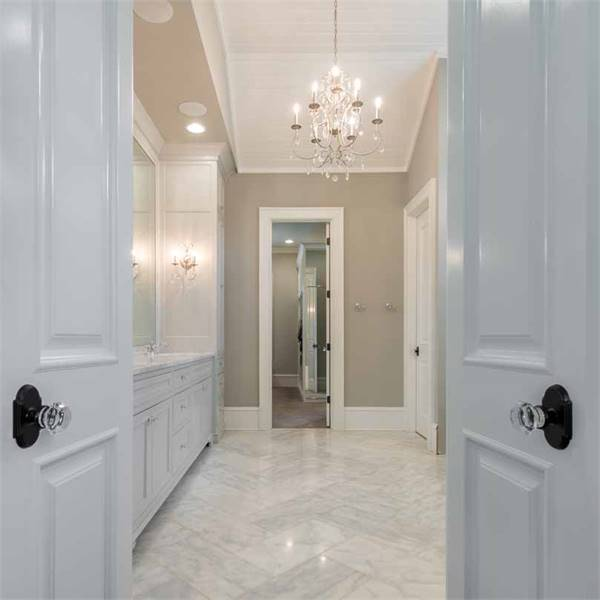 A white double door with crystal knobs open to the primary bathroom.