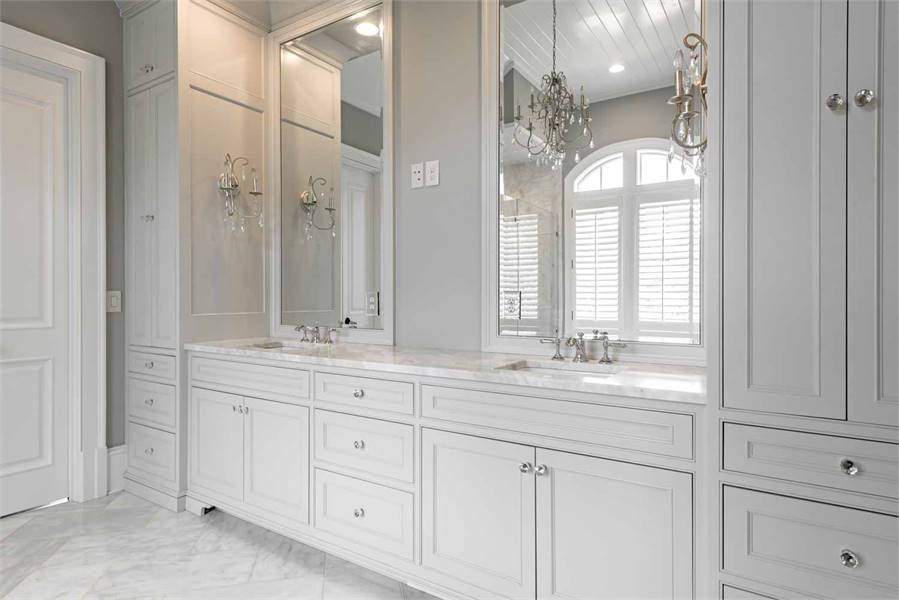 The primary bathroom includes a dual sink vanity with marble countertop flanked by white cabinets.