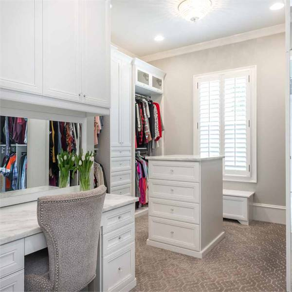 Walk-in closet with built-in wardrobe and an island counter matching with the vanity.
