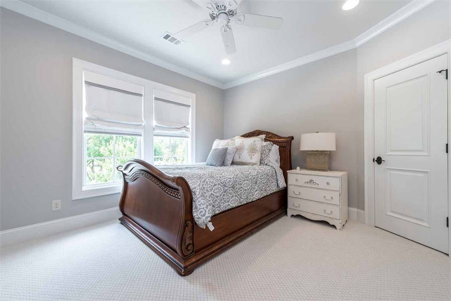 Bedroom with a drawer nightstand and a wooden bed that stands out against the light gray walls and carpet flooring.