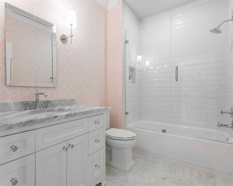 This bathroom offers a walk-in shower, a toilet, and a marble top sink vanity paired with a chrome framed mirror.