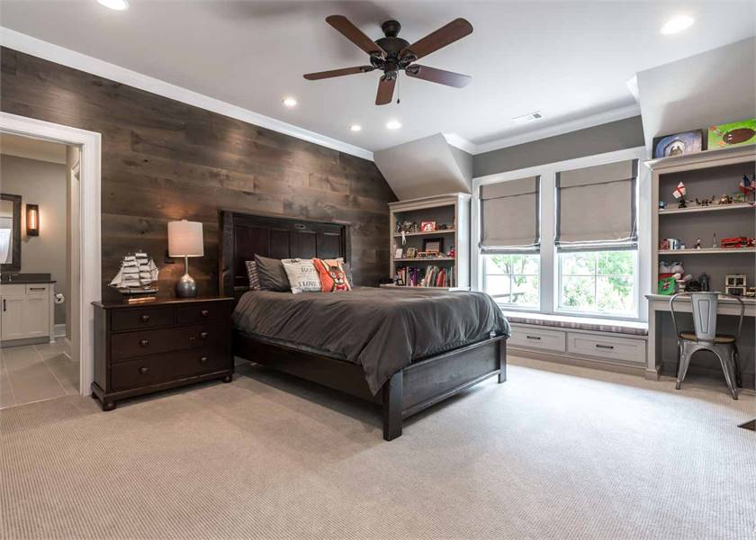 Kid's bedroom with wood-paneled accent wall and a window seat flanked by built-in shelves.