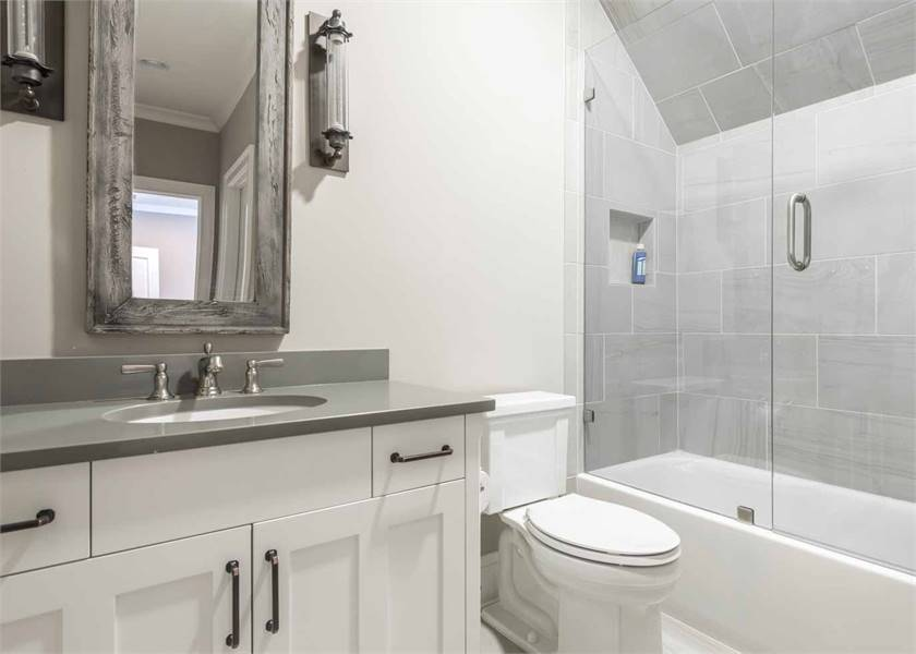 Kid's bathroom equipped with a toilet, walk-in shower and a sink vanity lit by cylindrical sconces.