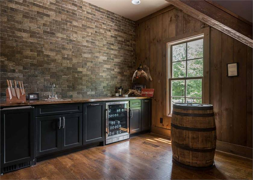 Wet bar with a barrel, beverage fridge and black cabinets fixed against the brick wall.