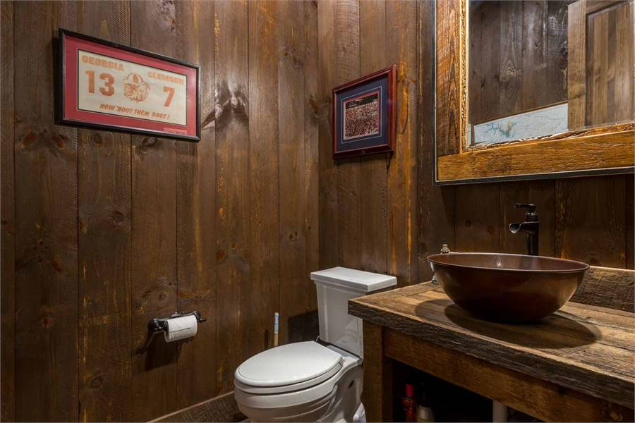 The powder room offers a toilet and a wooden vanity topped with an antique copper vessel sink.
