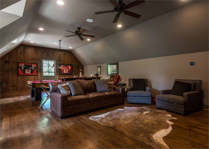 Game room with gray vaulted ceiling and a dark hardwood flooring topped by a cowhide rug.