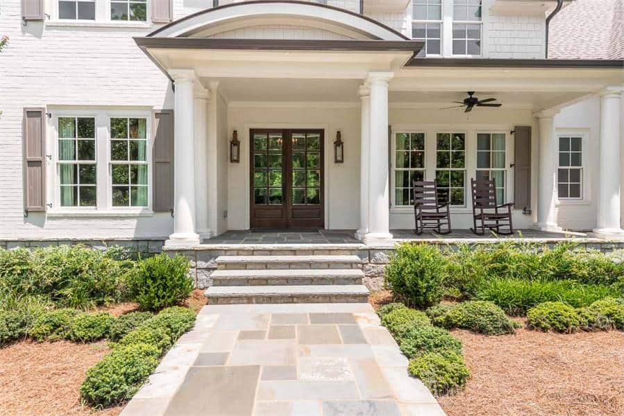 A closer look at the front porch shows the wooden french front door and decorative columns supporting the barrel roof.