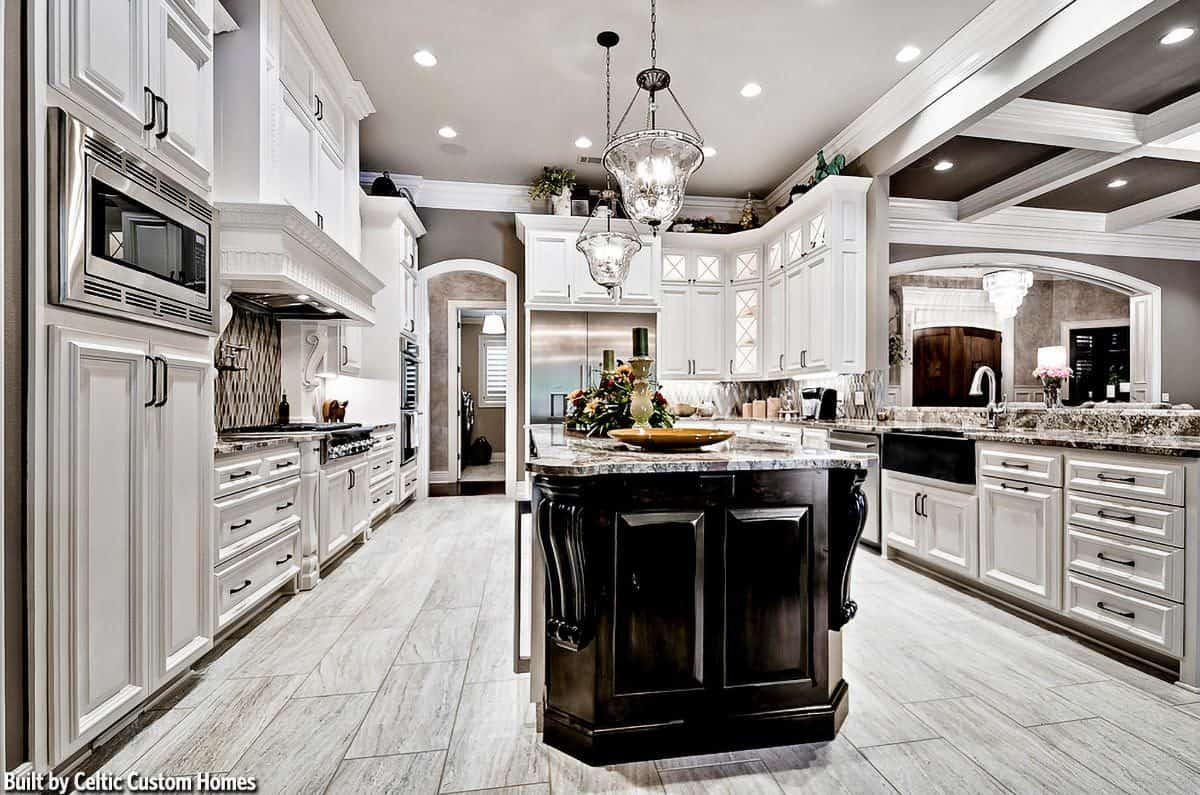 The kitchen is equipped with stainless steel appliances, a farmhouse sink, and a granite top island bar lit by glass pendants.