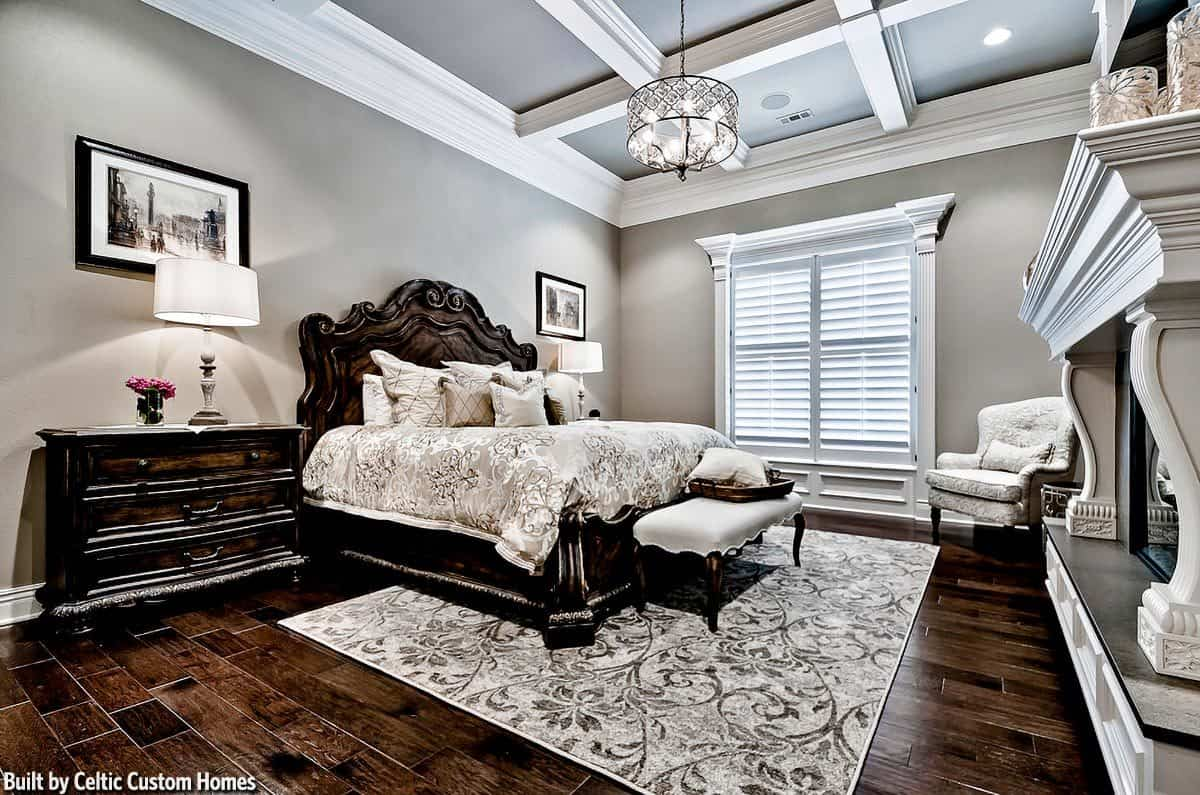 The primary bedroom has light gray walls and a coffered ceiling with hanging ornate drum chandelier.