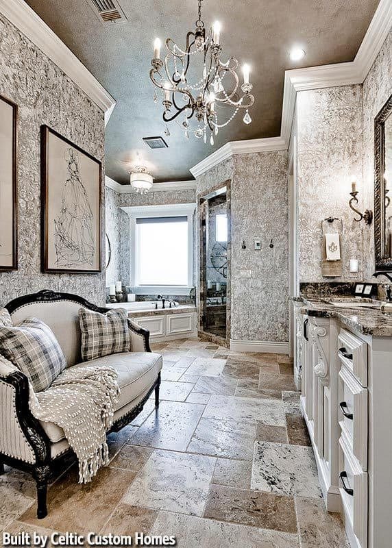Primary bathroom with a whirlpool corner tub, walk-in closet, and a sink vanity facing the cushioned sofa that's illuminated by a beaded chandelier.