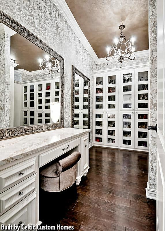 Walk-in closet with glass front cabinets and a marble top vanity paired with a velvet stool and large framed mirror.