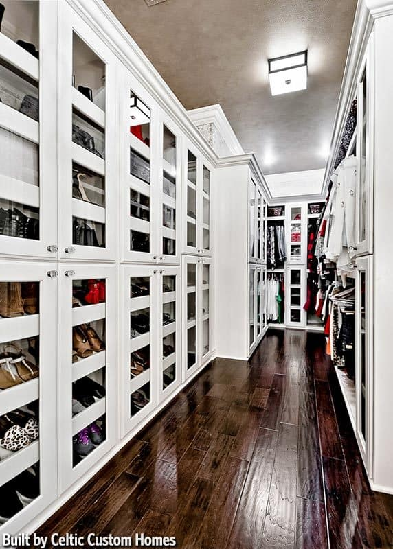 This walk-in closet offers plenty of storage. It has dark hardwood flooring and a regular ceiling mounted with a flush light.