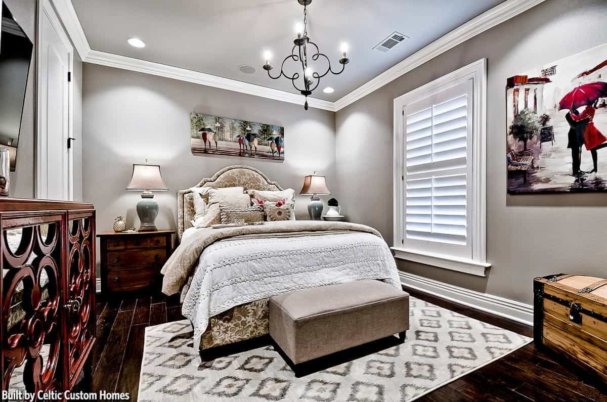 This bedroom has wide plank flooring and gray walls adorned by lovely paintings.
