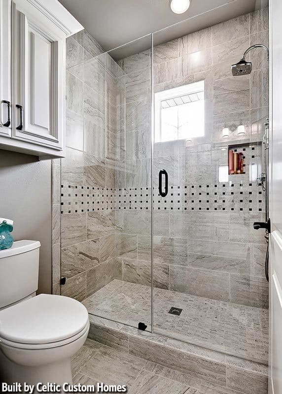 Bathroom with a walk-in shower and a toilet under the floating white cabinet.