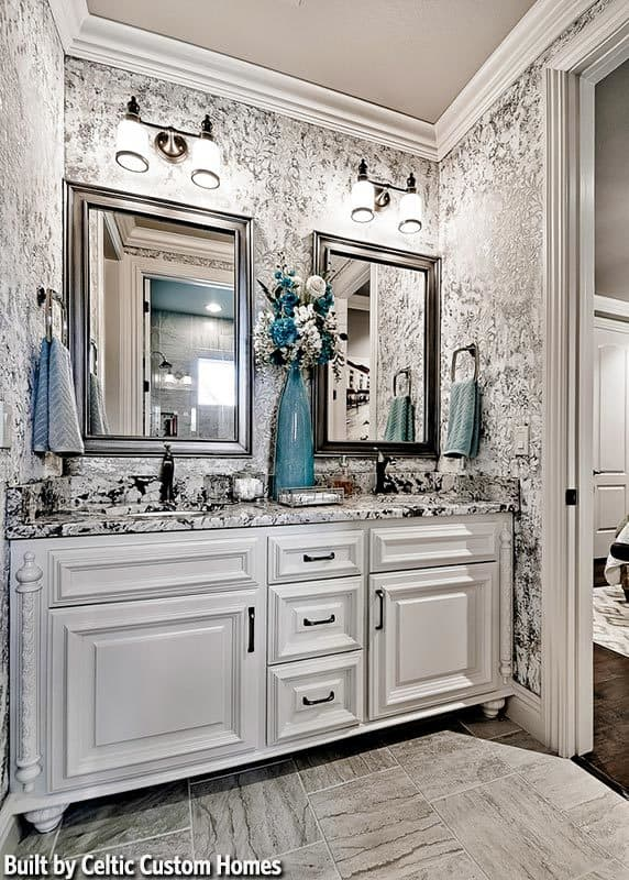 Powder room with dual sink vanity complemented by framed mirrors and glass sconces fixed against the gray patterned wallpaper.