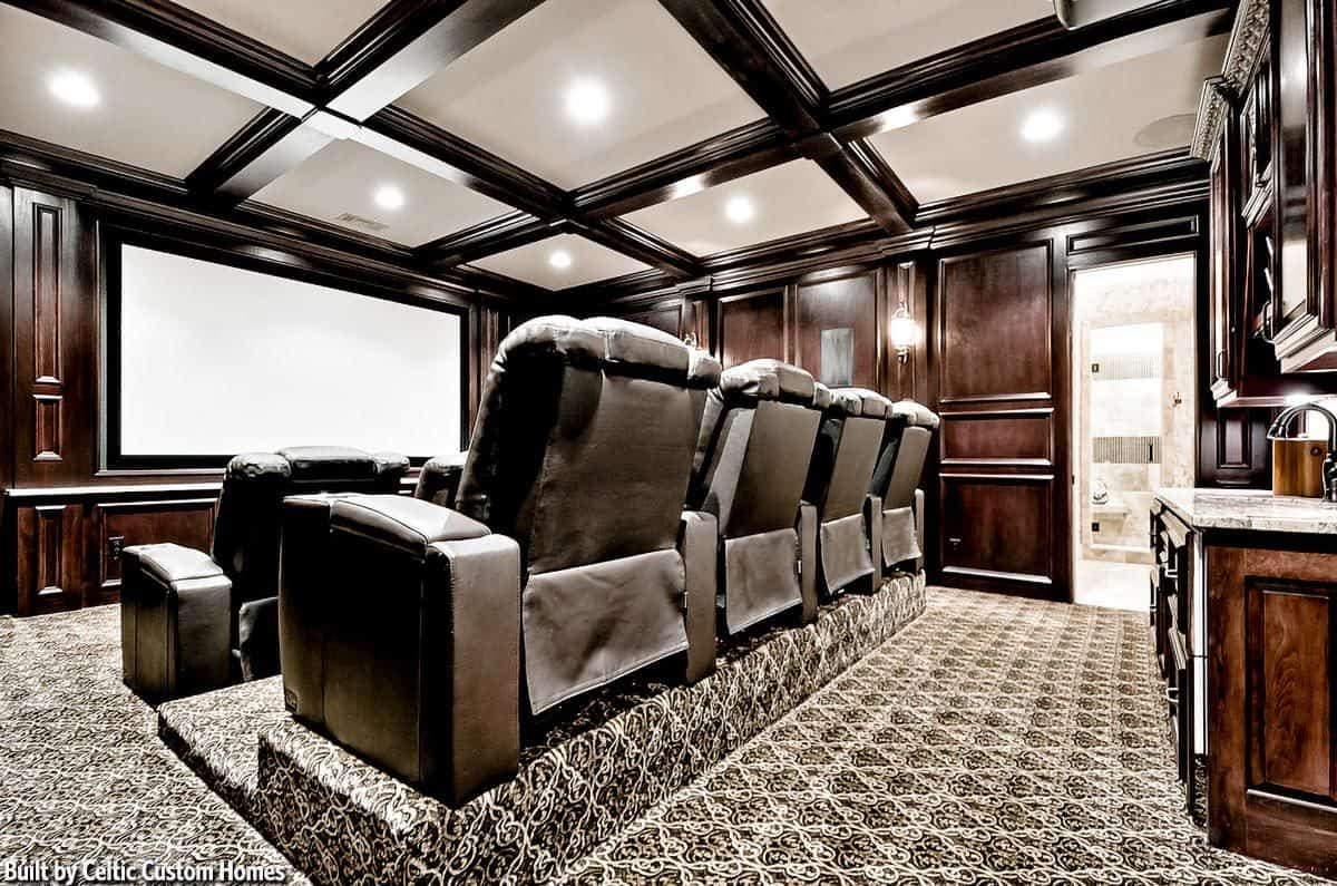 The home theater has lovely carpet flooring and a coffered ceiling fitted with recessed lights.
