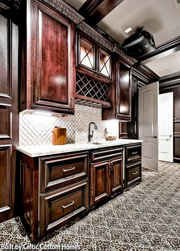 A closer look at the wet bar with a white marble countertop, undermount sink, dark wood cabinets, and wine shelves.