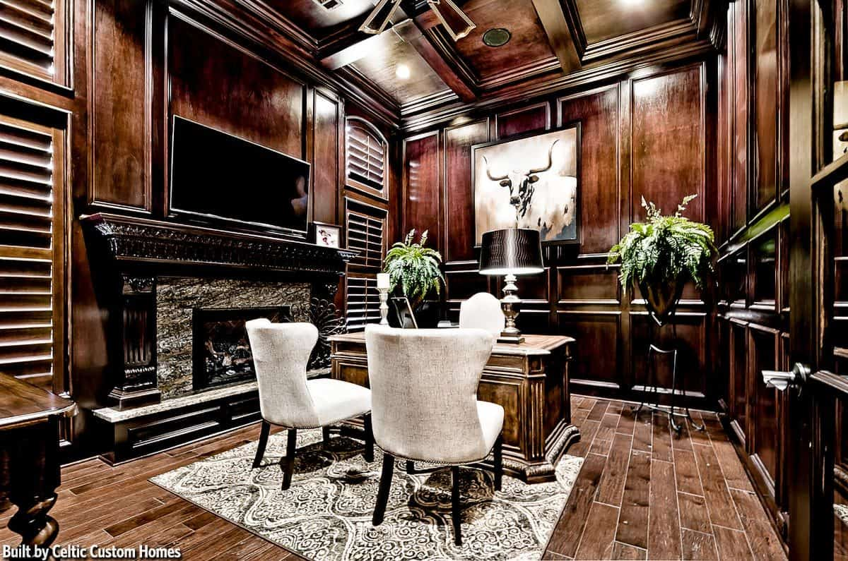Home office with a warm fireplace, wingback chairs, a wooden desk, and dark wood coffered ceiling matching with the wood-paneled walls adorned by a bull artwork.