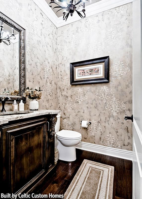 A beautiful wallpaper sets an elegant backdrop to this powder room with a toilet and sink vanity complemented with a bordered runner.