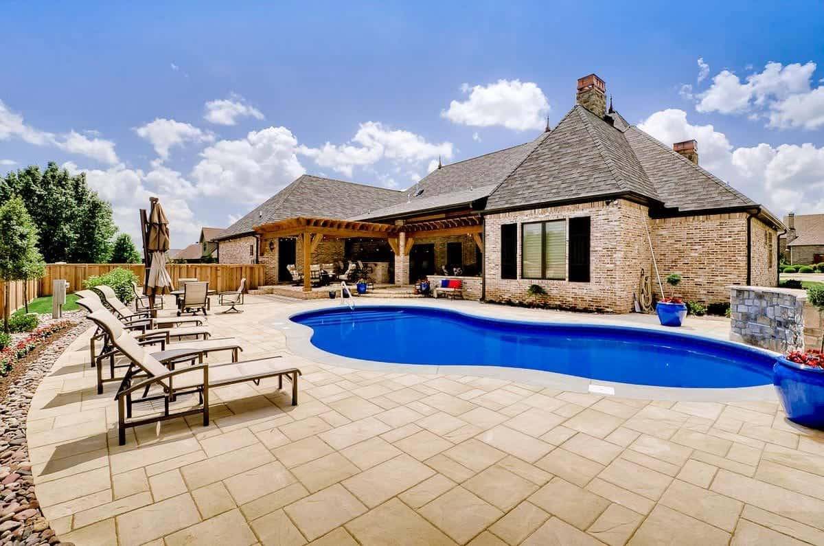 Home's rear exterior view showing the outdoor living and a freeform pool with tiled paving.