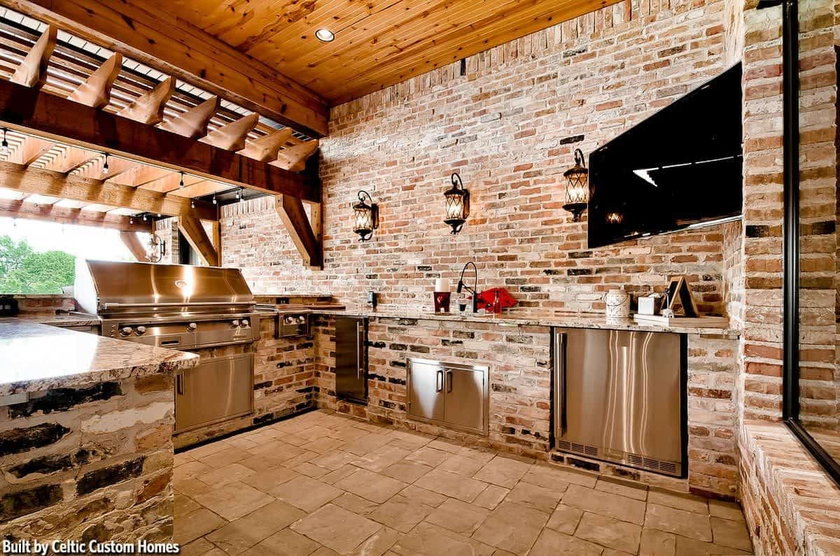 Outdoor kitchen with stainless steel appliances and cabinets along with a corner TV fixed against the brick walls.