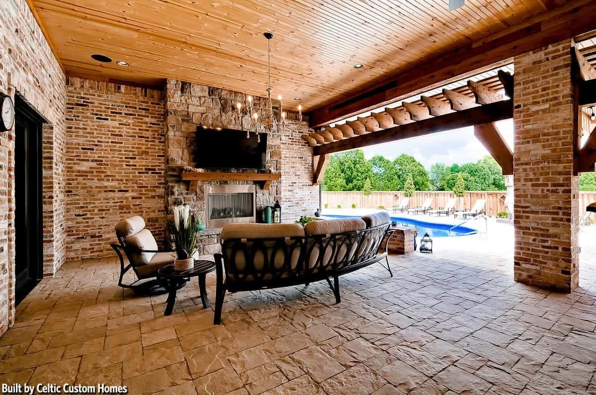 Outdoor living with cushioned seats and a glass-enclosed fireplace under the wall-mounted TV.