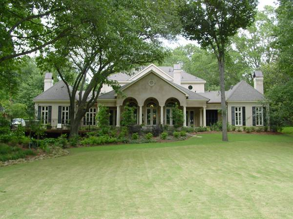 Rear view of the house from the lush backyard shows the columns and veranda framed with arches.