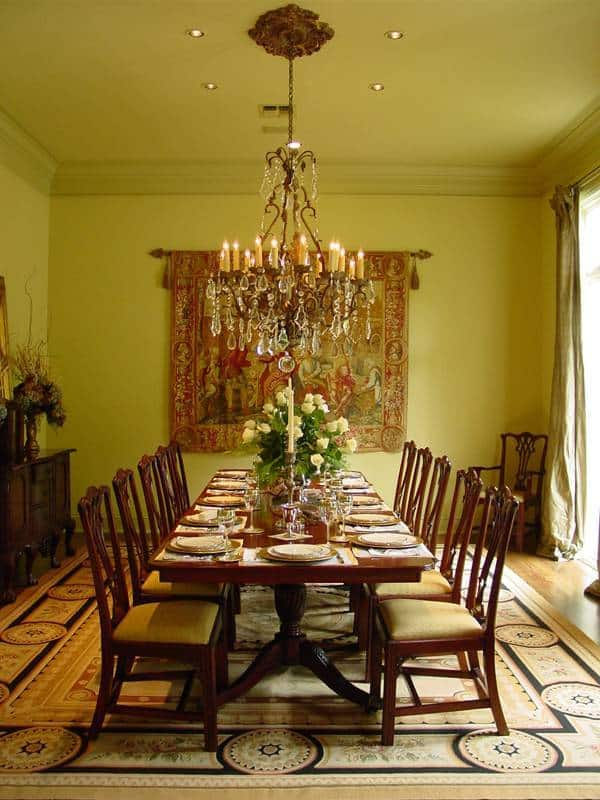The formal dining room is decorated with a classic tapestry and a crystal chandelier hanging over the wooden dining set.