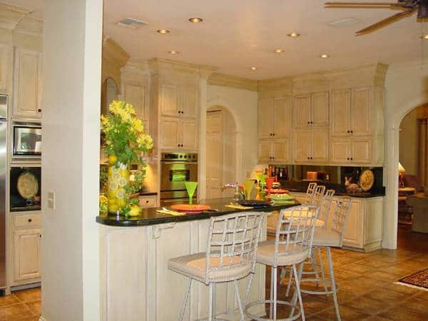 The kitchen has black granite countertops, white cabinetry, and a peninsula paired with cushioned chairs.