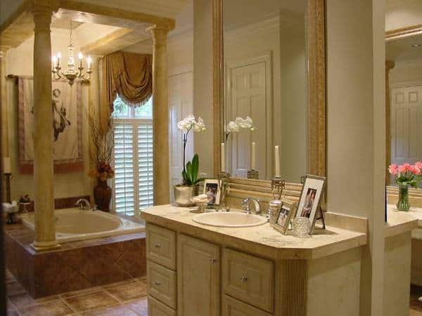 The primary bathroom is equipped with sink vanity and a deep soaking tub illuminated by a candle chandelier.