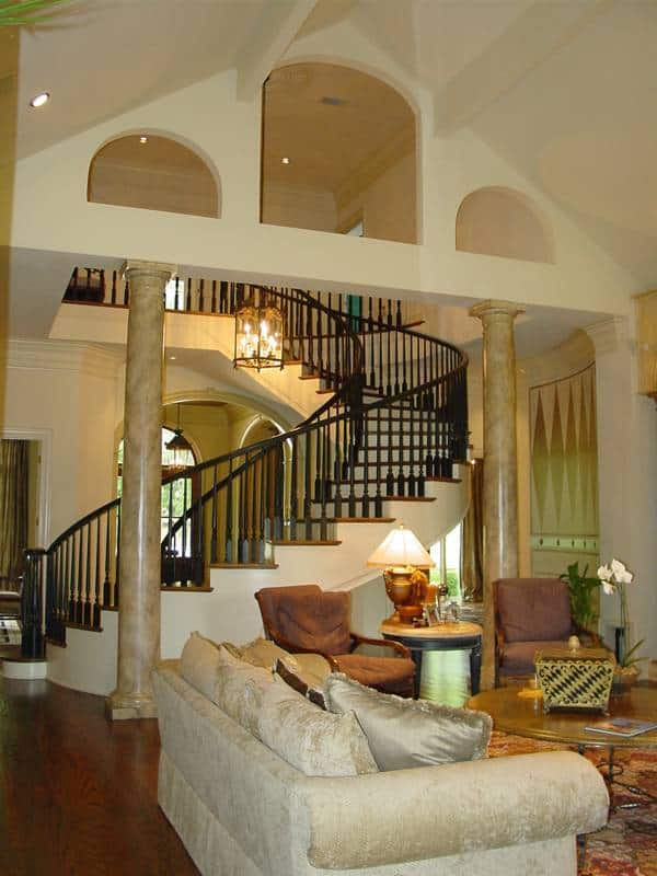 Living room next to the winding staircase with rich hardwood flooring and a cathedral ceiling supported by marble columns.