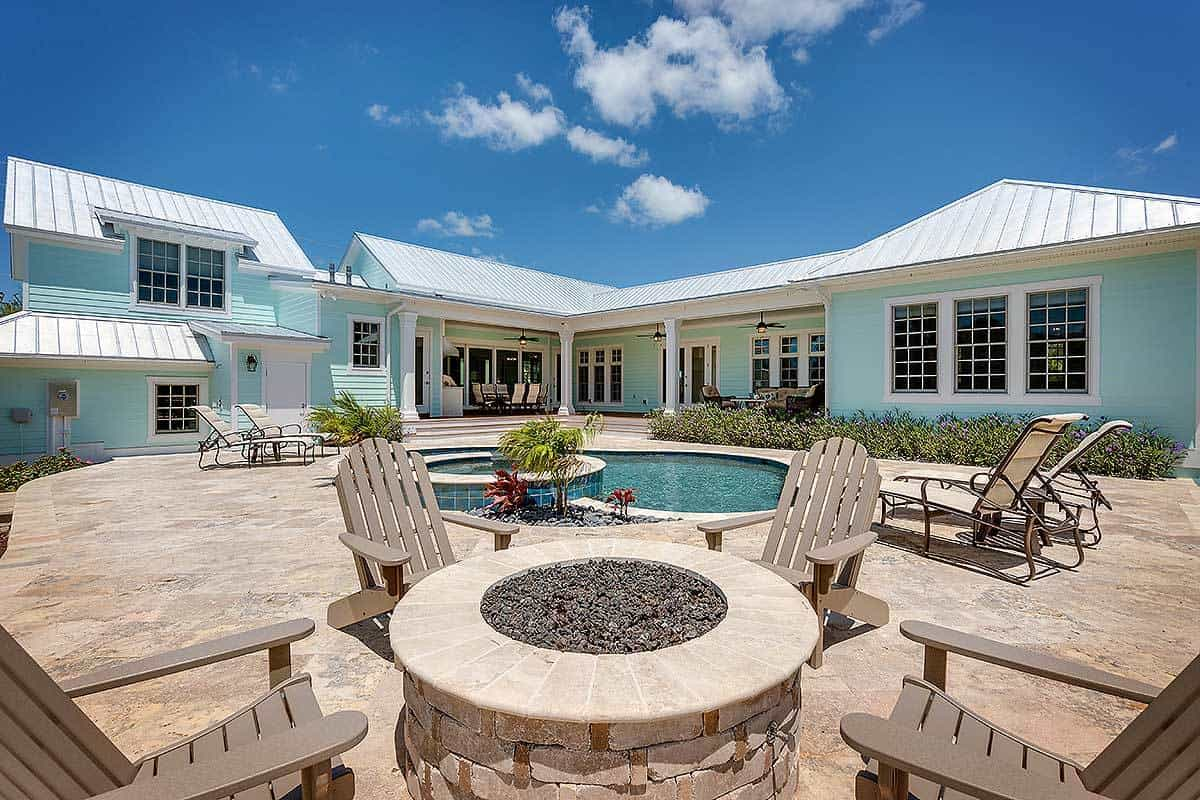 A further view shows the fire pit seating across the pool surrounded by wooden loungers.