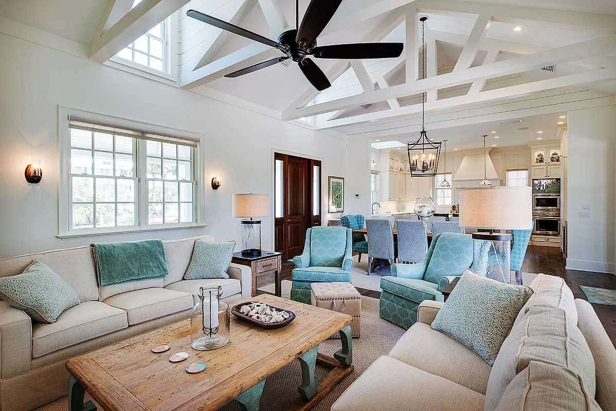 Living room with cozy seats and a cathedral ceiling framed with decorative beams.