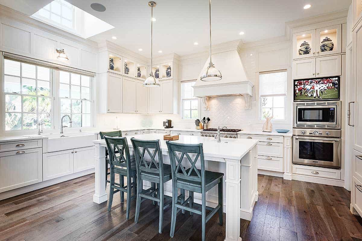 Kitchen with white cabinetry, stainless steel appliances, and an island bar lined with gray counter chairs.