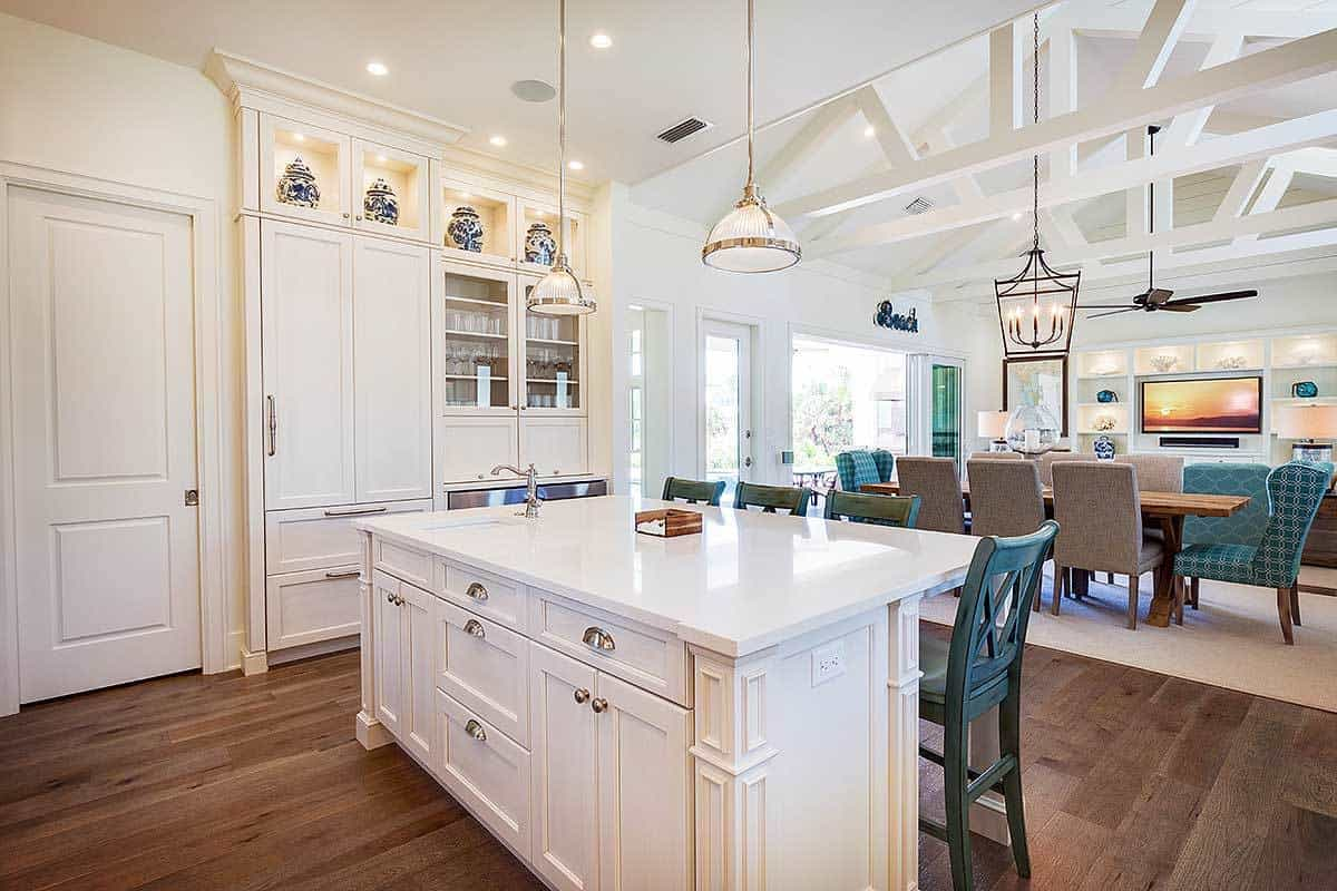 A pair of glass dome pendants along with recessed ceiling lights illuminate the island bar and inset cabinets.