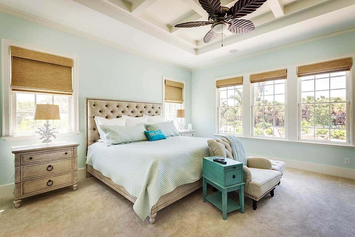 A comfy tufted bed, light wood nightstands and a striped armchair flanked by a green side table and ottoman fill the primary bedroom.