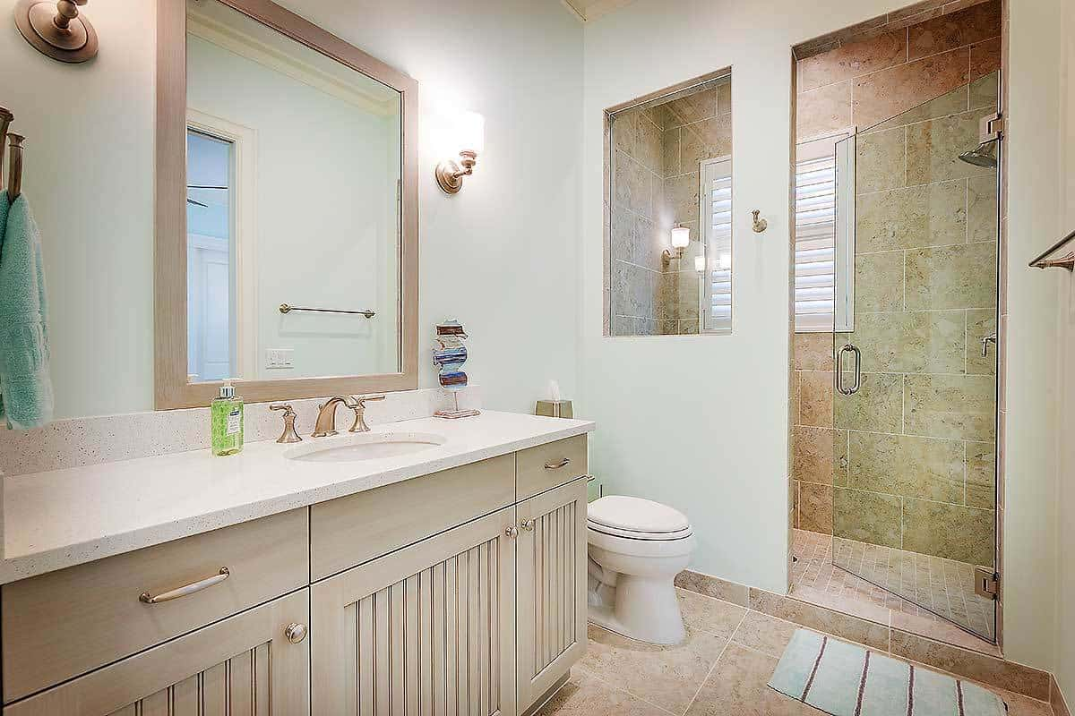 This bathroom offers a light wood vanity, a toilet, and a walk-in shower with a glass window and door.