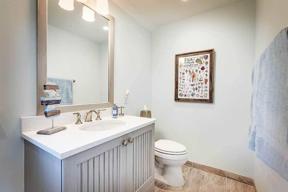 Bathroom with a sink vanity, a toilet, and a wooden framed artwork fixed against the light blue walls.