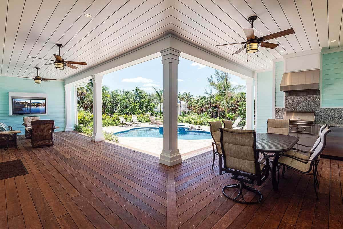 Covered lanai filled with outdoor living area and a kitchen complemented with a dark wood dining set.