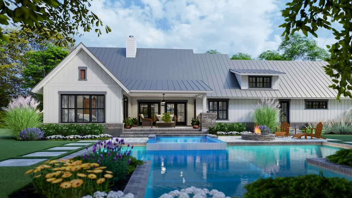 The home's rear view with serene landscaping surrounding the swimming pool.