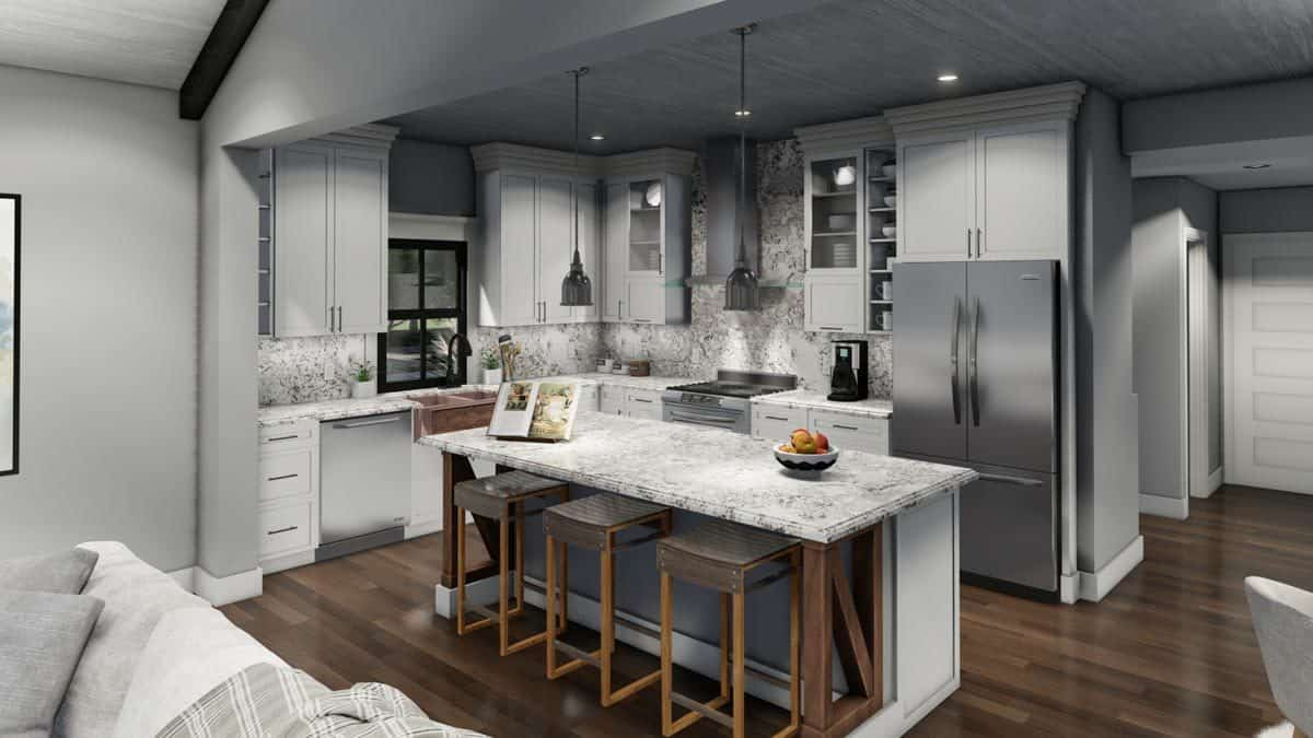 A closer look at the kitchen with gray cabinetry and a granite top breakfast island.