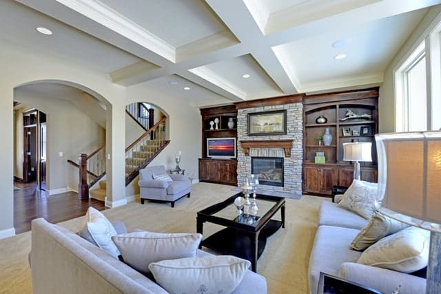 Living room with beamed ceiling and a stone fireplace flanked by wooden built-ins.Living room with beamed ceiling and a stone fireplace flanked by wooden built-ins.