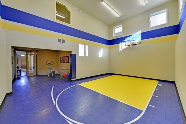 Sport court across the exercise area with a two-story ceiling and yellow walls with blue accents mounted with a ring.