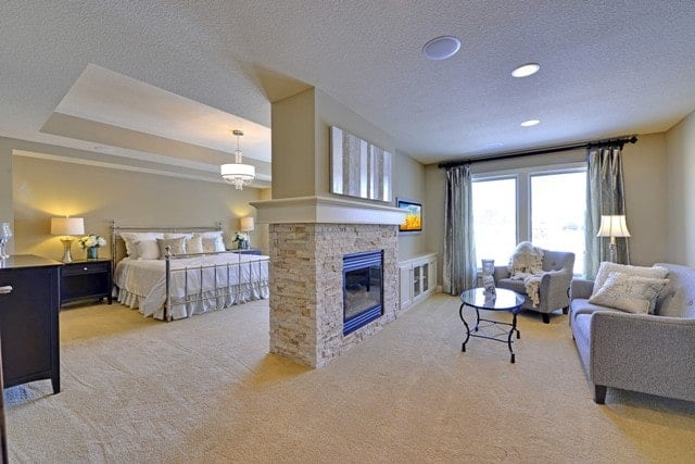 The spacious primary bedroom features a dual-sided fireplace that serves both the sleeping and sitting area.