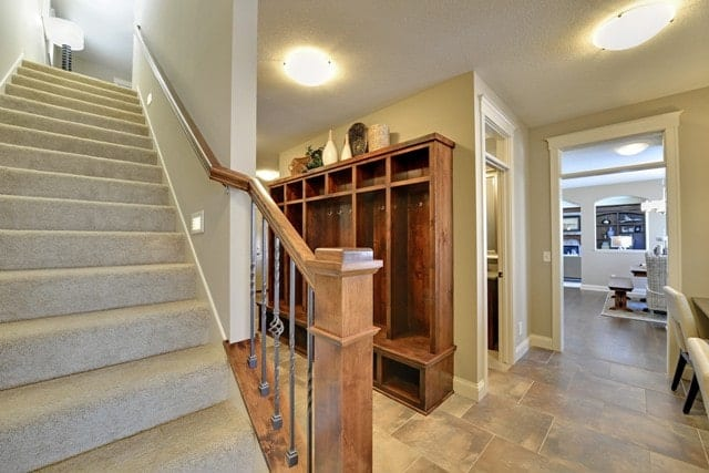 Mudroom rear staircase covered in a beige carpet.
