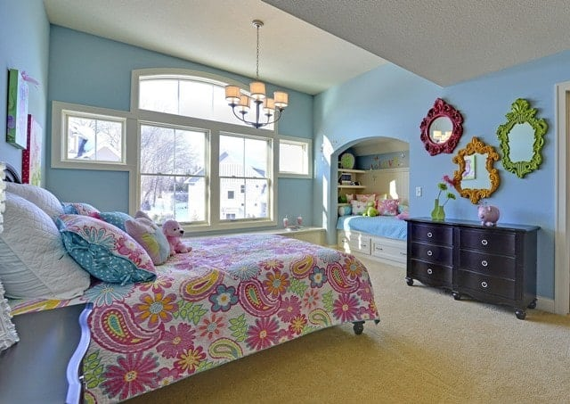 Princess suite with a sleepover bunk and light blue walls adorned by multi-colored mirrors.