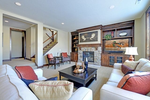 Family room with a fireplace, dark wood coffee table, and comfy beige seats accented with fluffy pillows.