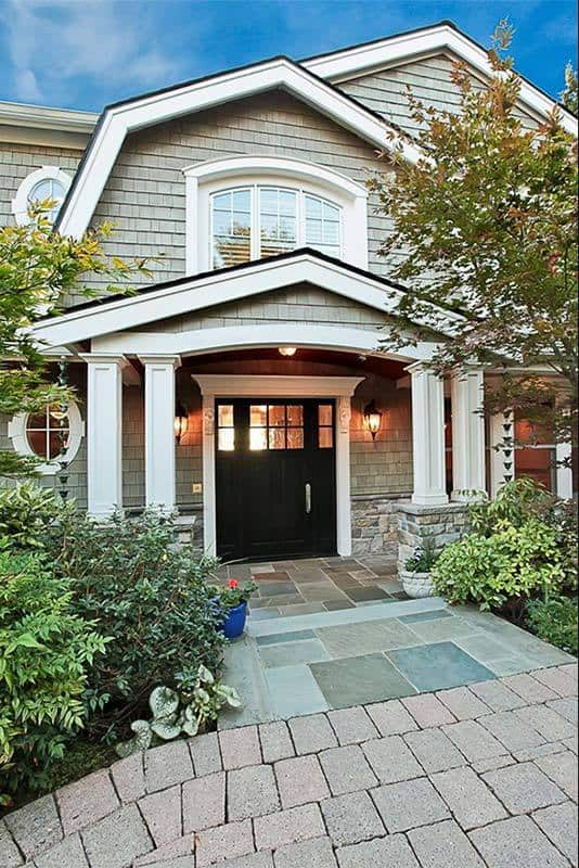 A close up look at the home's portico supported by wainscoted columns. It has a dark wood front door lit by warm sconces.