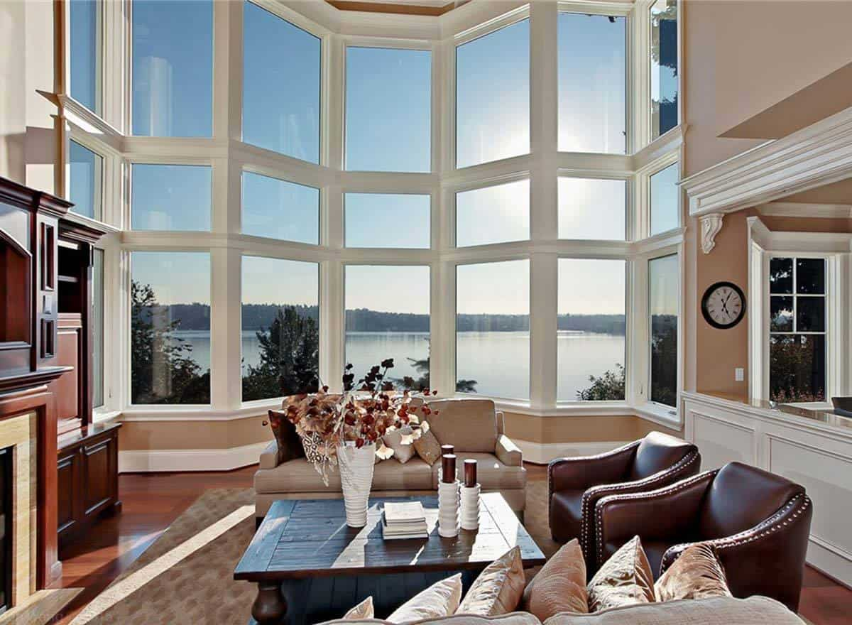 Living room with cozy seats and massive glazed windows overlooking the scenic view.