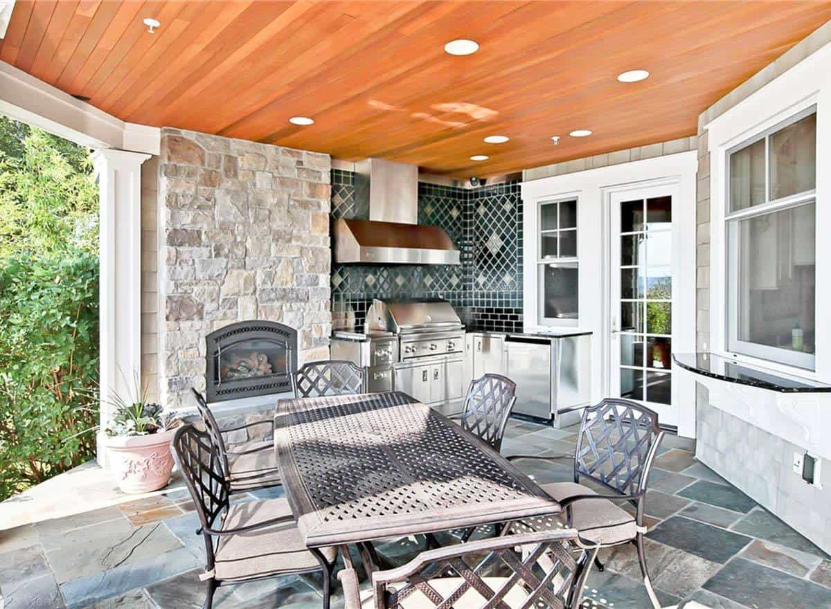 Covered patio with outdoor kitchen, metal dining set, and a stone fireplace.